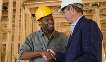 2 men in hard hats shaking hands on construction site